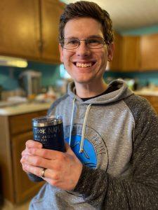 Pastor Josh holding his favorite coffee tumbler.